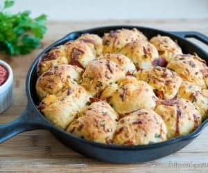Skillet-Baked Pepperoni Garlic Knots are a great football food recipe - Pizza dough is tied and tossed with pepperoni, garlic, and cheese