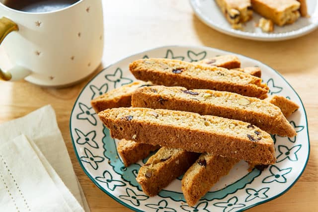 Cranberry Orange Biscotti - On a Blue Plate Stacked with Cup of Coffee On Side