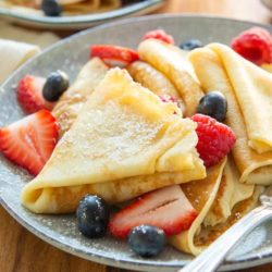 Crepes On a Plate Dusted with Powdered Sugar and Served with Berries