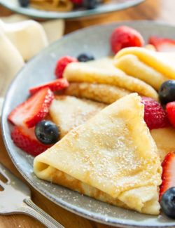 Crepes - On a Plate Dusted with Powdered Sugar and Served with Berries