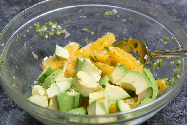 Orange Segments, Jalapeno, Herbs, and Shallot in a Glass Bowl with Avocado Chunks Added