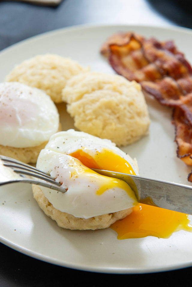 How to Make Poached Eggs - End View on a Plate with Knife Showing Runny Yolk