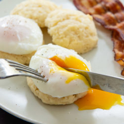 Cutting a Poached Egg On Top of a Biscuit with Bacon