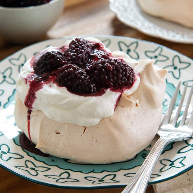 Pavlova Dessert Recipe - on Blue Plate with Whipped Cream and blackberry sauce
