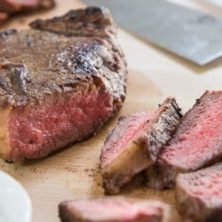 Pan Seared Steak Sliced On a Cutting Board and Shown Cooked Rare