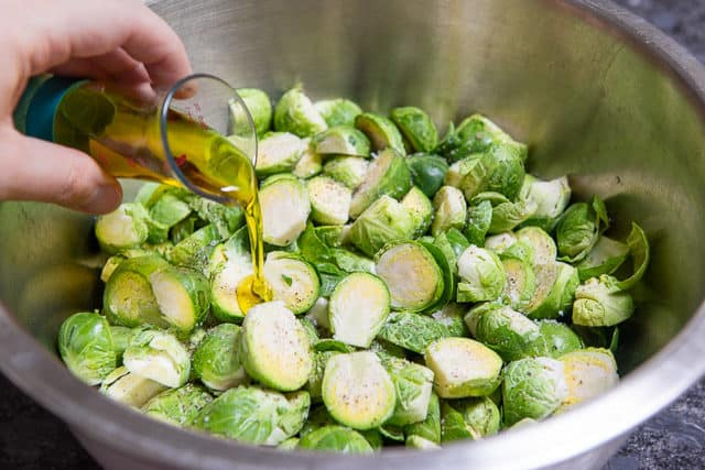 Pouring Olive Oil on Halved Brussel Sprouts in Bowl