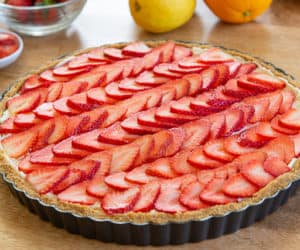 A strawberry tart inside of metal tart pan with fresh citrus surrounding
