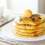 Cornmeal Pancakes Stacked on a Plate with Butter and Maple Syrup Pouring On Top