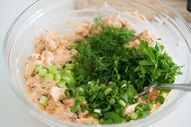 Green onion, dill, parsley, and celery Added to Salmon Salad Recipe In Bowl