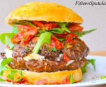 Caprese Burger - Shown on a Plate with Mozzarella Cheese Oozing from Center and Tomato Basil Relish on Top