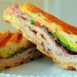 Cuban Sandwich Sliced in Half on White Plate