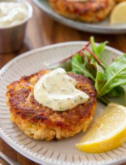 Crab Cakes - Served on Plates with Dollop of Tartar Sauce and Lemon Wedge