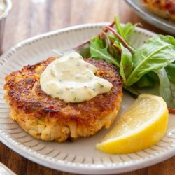 Crab Cakes Served on Plates with Dollop of Tartar Sauce and Lemon Wedge