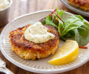 Panko Crab Cake Recipe - served on a White Plate with Lemon, Tartar Sauce, and Greens