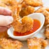 Crispy Coconut Shrimp Dipped Into Sweet Chili Sauce With Platter Of Coconut Shrimp Around It