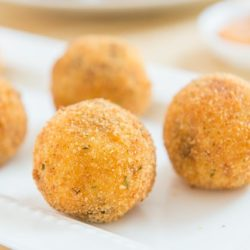 Potato Croquettes On a White Platter with Dipping Sauce in background