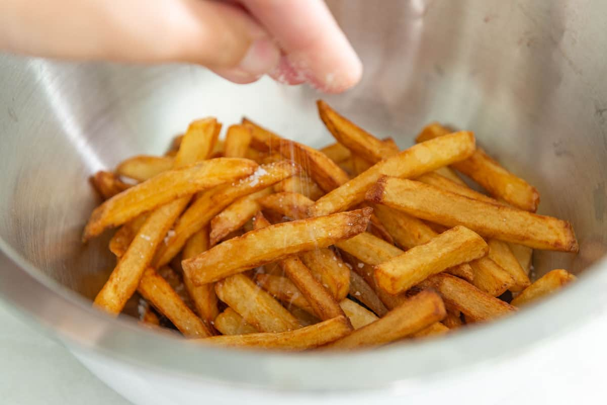 Seasoning Deep Fried French Fries with Salt in Bowl