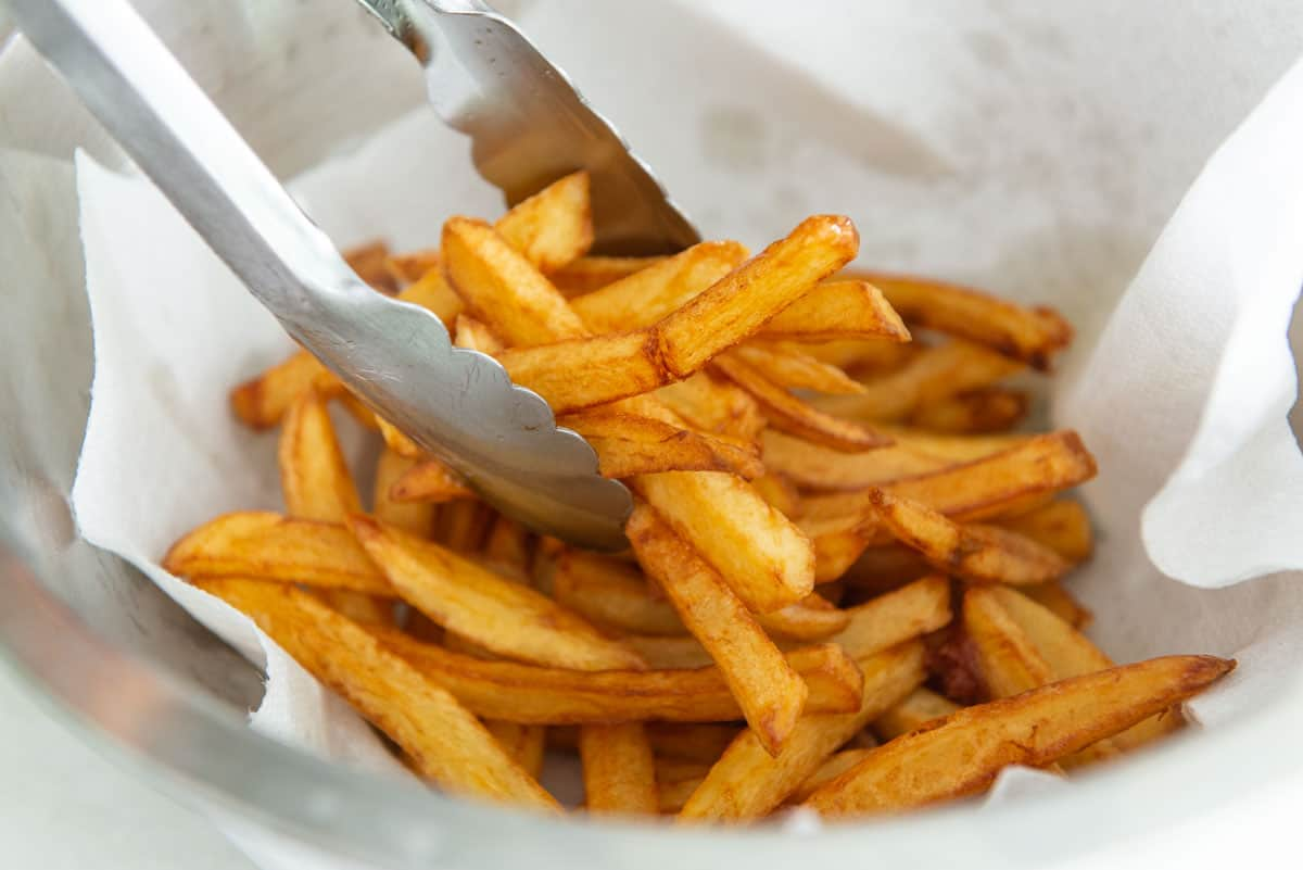 Placing the Freshly Double Fried French Fries Onto a Paper Towel to Drain