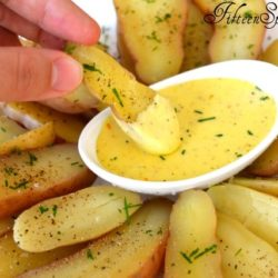 Roasted Fingerling Potatoes - Dipping Into Aioli with Herbs and Pepper on Top