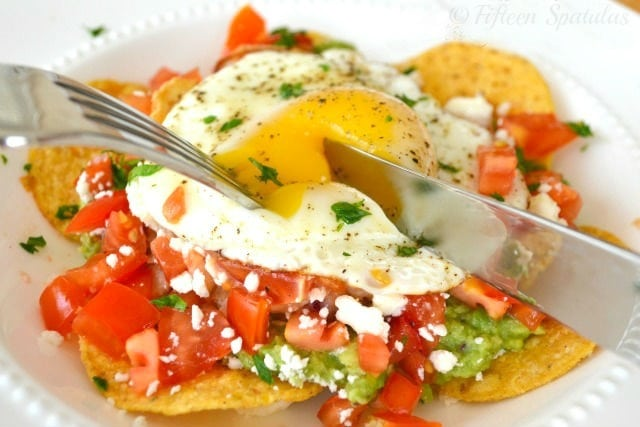 Huevos Rancheros - On White Dish with Fork and Knife Cutting Into Runny Yolk