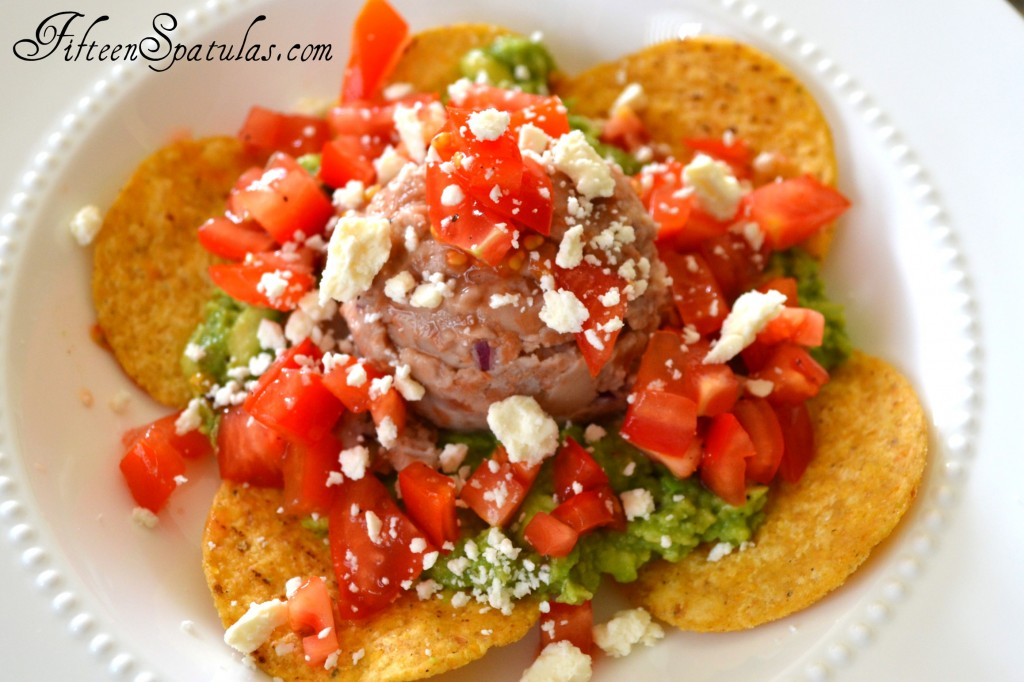 Huevos Rancheros with Tortilla Chips, Guacamole, Bean Scoop, Tomato, and Cheese On a Plate