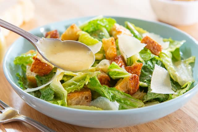 Caesar Salad Recipe - in Blue Bowl with homemade Dressing Spooned On top