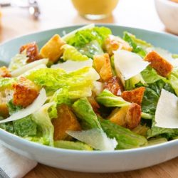 Caesar Salad In a Blue Bowl with Croutons and Parmesan Shavings