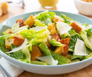 Cesar Salad - In Blue Bowl with croutons and Parmesan Shavings
