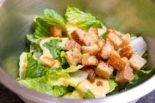 Caesar Salad Ingredients - In Mixing Bowl with Romaine, Dressing, and Croutons