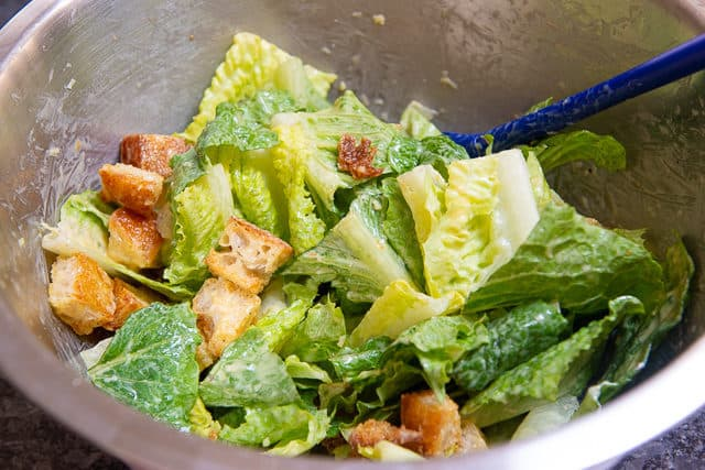 Tossing Romaine and Croutons In Bowl with Dressing