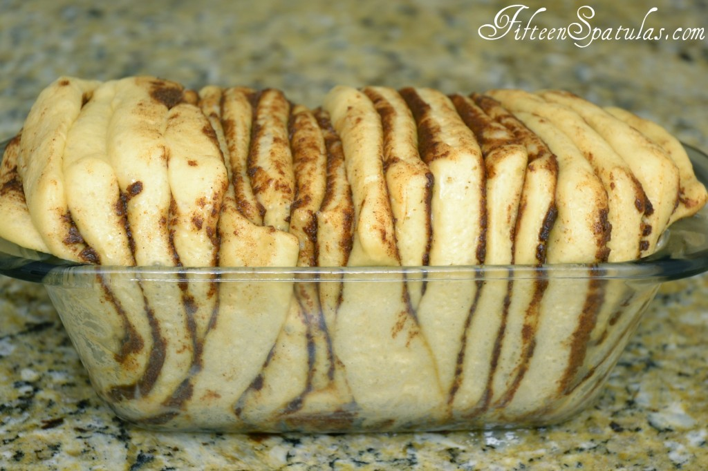 Fully Expanded Raw Cinnamon bread Dough in Glass Loaf Pan