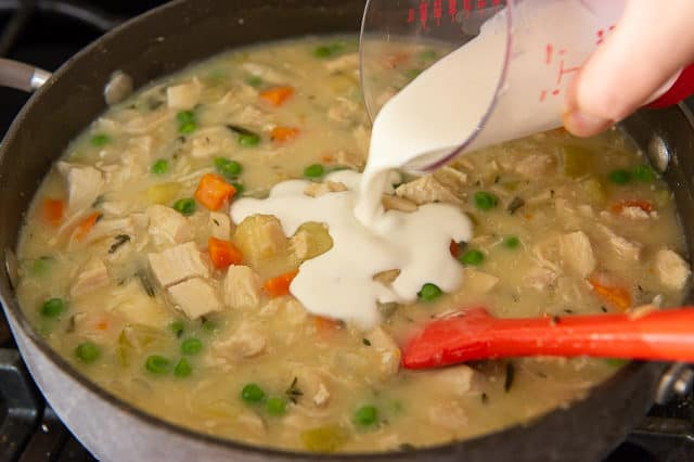 Pouring Heavy Cream Into Homemade Chicken Pot Pie Filling