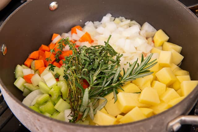 Chopped Carrot, Celery, Onion, and Potato In Pot with Herbs