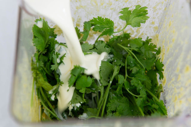 Pouring Cream Into Blender with Poblanos and Cilantro
