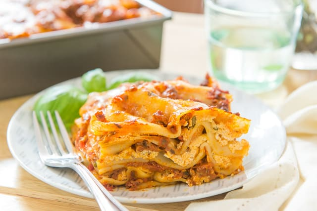 Easy Lasagna - Shown in Square Cut Garnished with Basil and Made With Quick Meat Sauce and Ricotta Filling