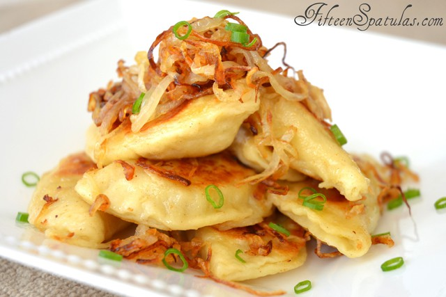 Fried Pierogies - In White Dish with Onions On Top