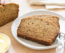 Banana Bread Slices on a White Plate with Remaining Loaf on Wooden board