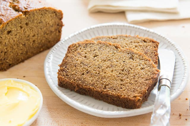 Banana Bread Sliced and Plated on White Dish with Remaining Loaf on Board