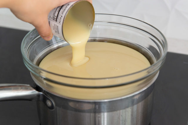 Pouring Sweetened Condensed Milk Into a Double Boiler