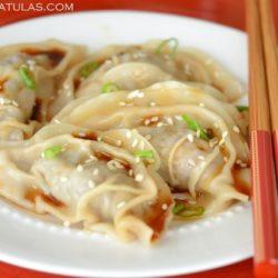 4 Asian Dumplings on White Plate with Chopsticks
