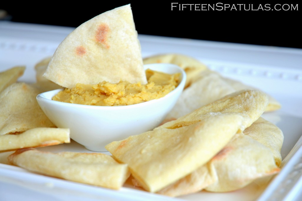Homemade Pita Bread Triangles on White Platter with Hummus Bowl