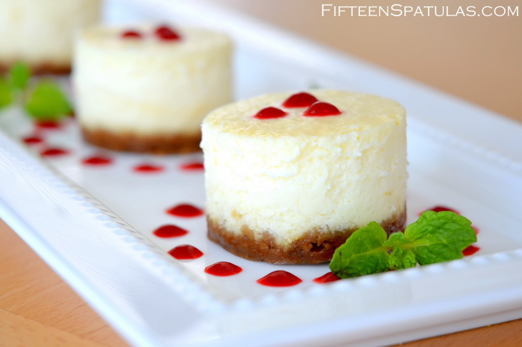 Mini Cheesecakes on White Platter with Raspberry Sauce and Gingersnap Crust