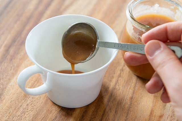 Adding Homemade Caramel Sauce and Milk to White Cup