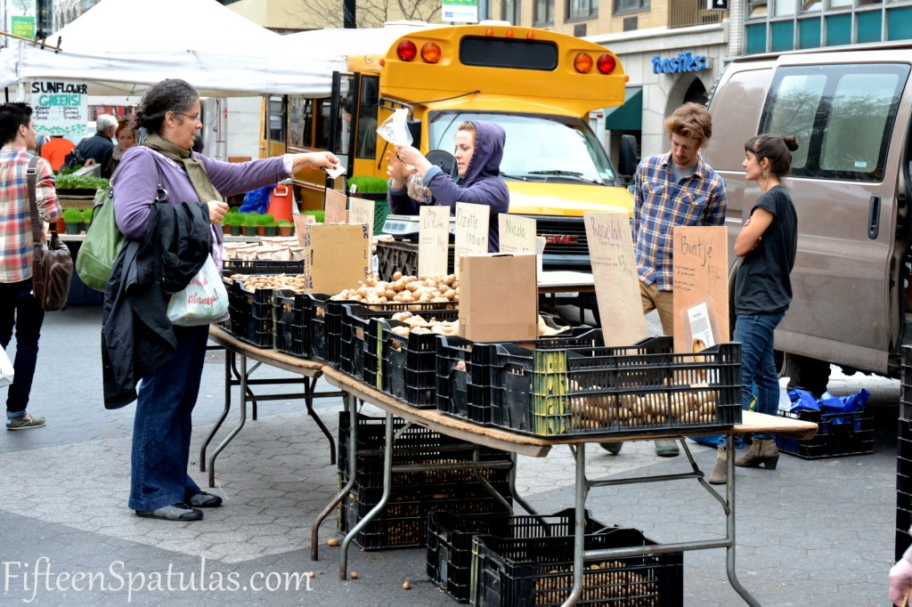 A group of people standing outside of a food truck farmers market