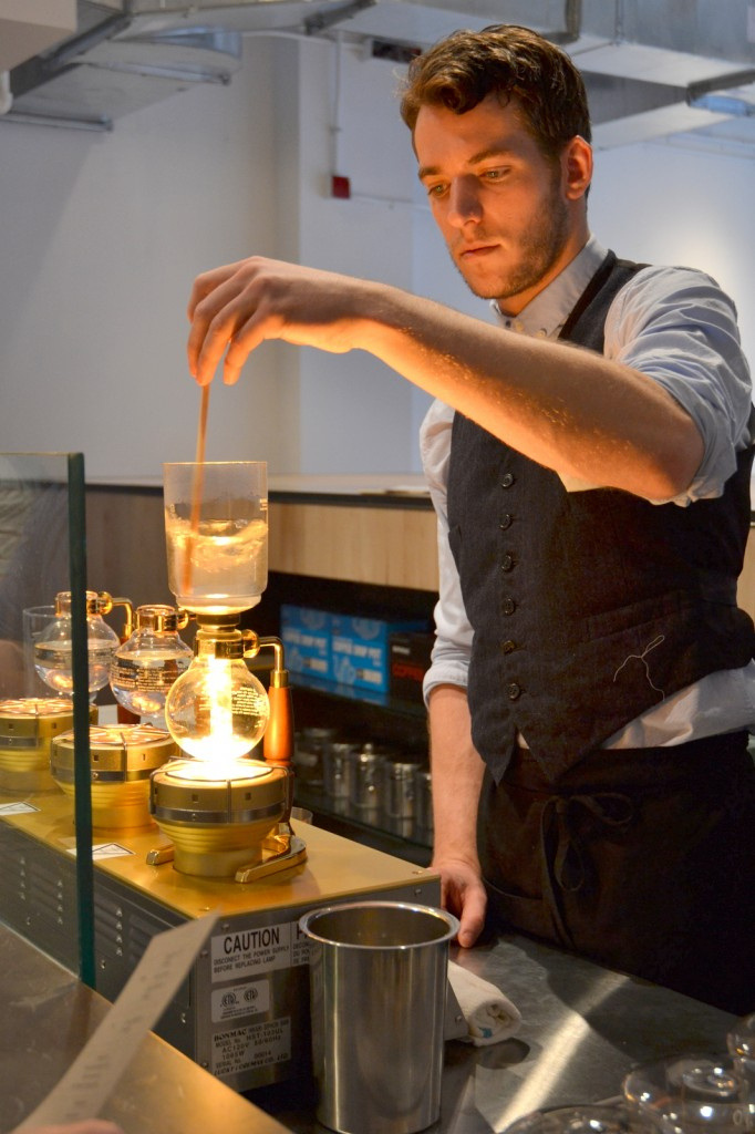 A man standing in a coffee bar preparing siphon coffee