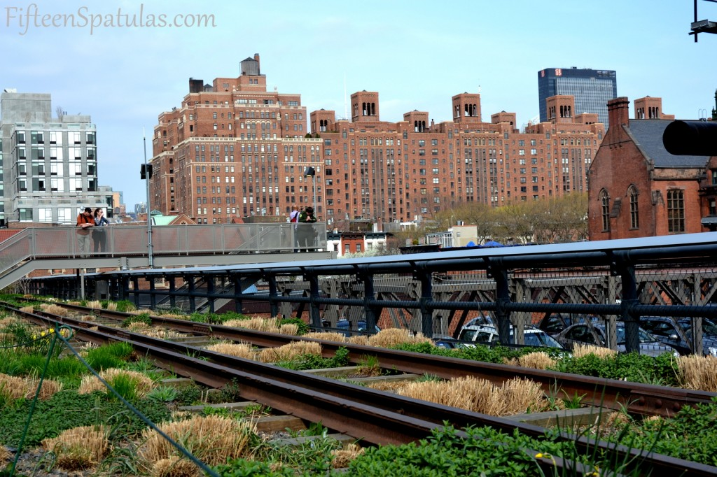 A train on a train track with buildings in the background with High Line in the background