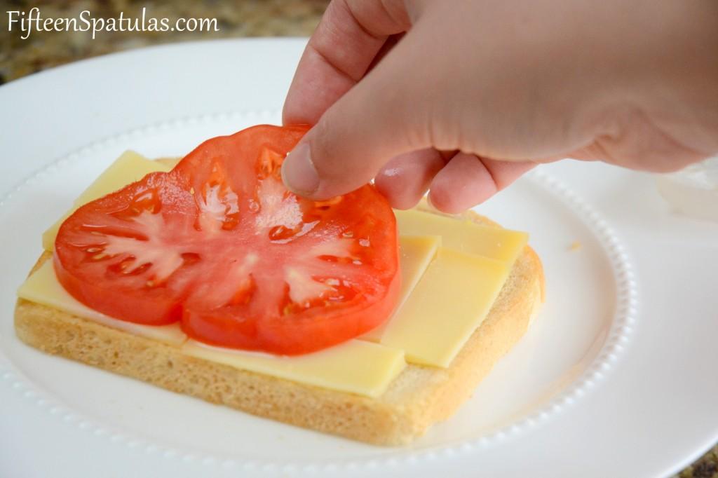 Adding Tomato to Gruyere Slices on Bread