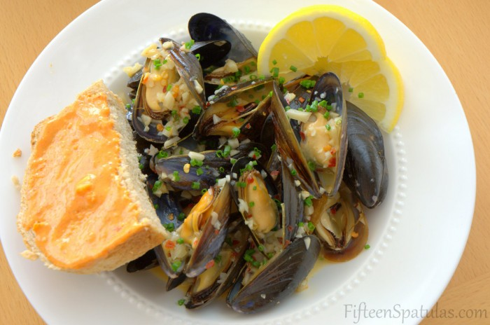 Steamed Mussels in Bowl with Lemon Wedges and Rouille Slathered Bread