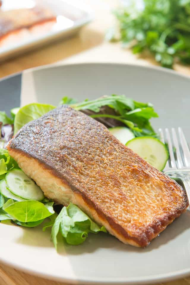 Pan Seared Salmon - Served Over a Bed of Greens On Plate