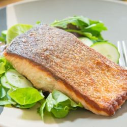 Pan Seared Salmon Served Over a Bed of Greens On Plate
